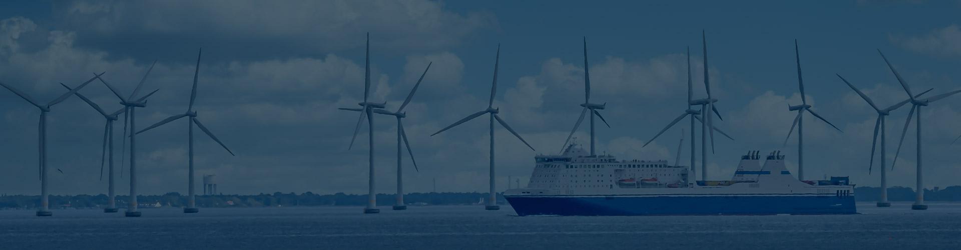 Blue ship passing windturbines at sea
